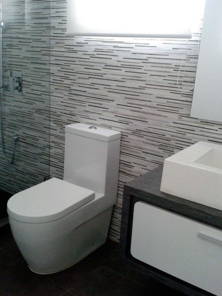 baño con pared de porcelanato de rayas horizontales de distintos tonos de grises, lavamanos rectangular con mueble laminado color wengue