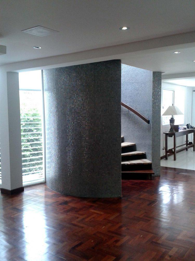 Escalera de caracol con muro revestido en mosaicos grises en la Casa E-2